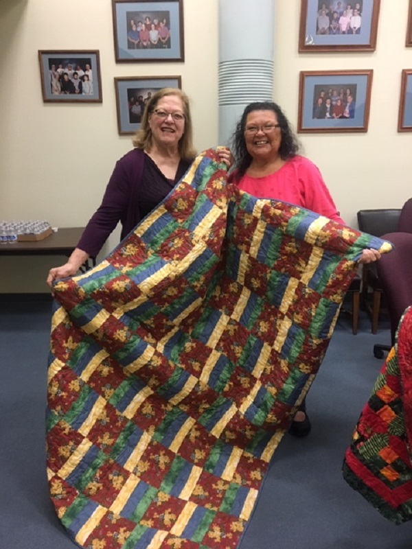 Cheryl Seidner presents a quilt to YSB Director Maura Eastman.